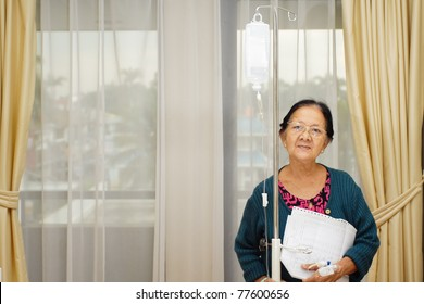 happy asian ethnic old woman patient in hospital ward with laboratory examination result on hand