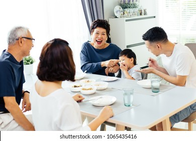 Happy Asian extended family having dinner at home full of laughter and happiness