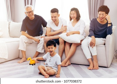 Happy Asian extended family sitting on sofa together and watching little child playing toy on the floor with happiness