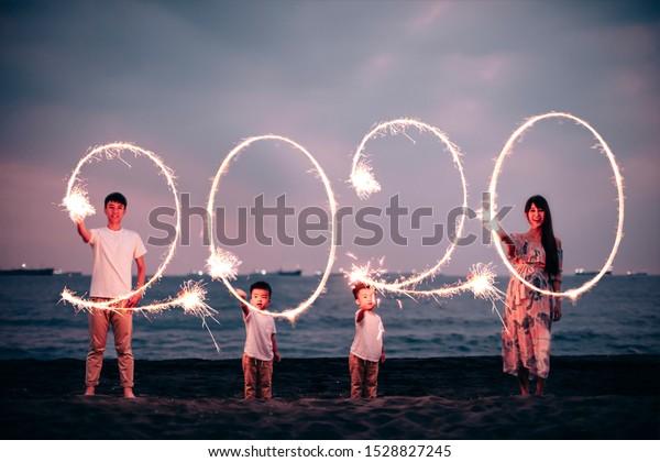 happy asian family celebrating new year 2020 on the beach