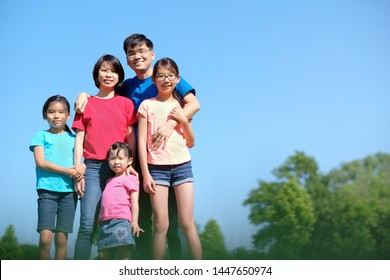 Happy Asian family with children outdoors in park during summer