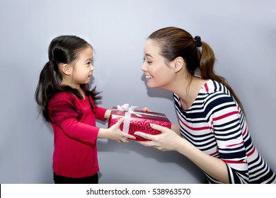 Happy Asian family, Daughter giving gift box to mother on grey background, Mother and daughter with red gift box, christmas day concept.