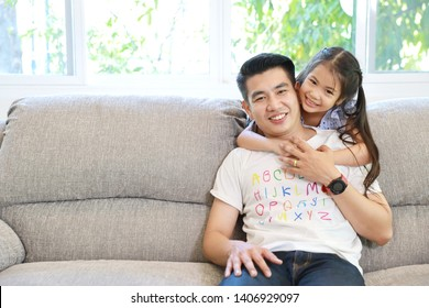 happy asian family daughter hugging father on grey sofa in living room with happy smiling face (lifestyle concept)