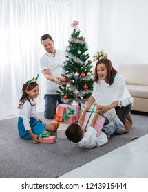 happy asian family decorate christmas artificial tree at home together