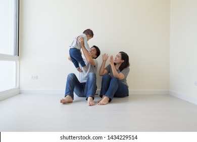 Happy Asian family with empty room in new house at moving day
