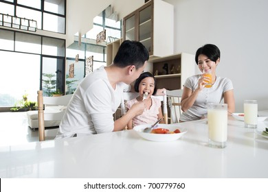 Happy Asian family enjoying a healthy snack at home.