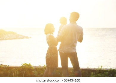 Happy Asian family enjoying outdoor activity together, standing on coastline in beautiful sunset during holiday vacations.