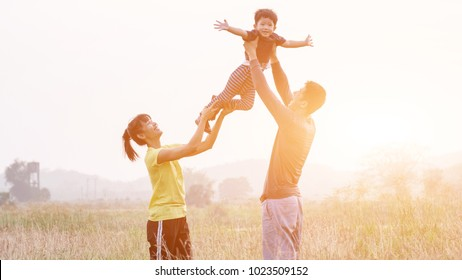 Happy Asian Family Enjoying Family Time Together in the Meadow