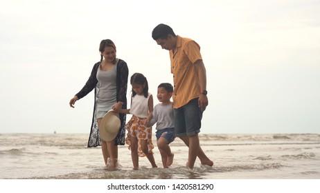 Happy asian family enjoying walk on the beach