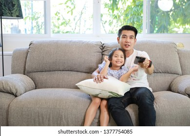 Happy Asian family, father and daughter are watching TV on the sofa in the living room and he is pressing the remote with a smiling face (relaxation and technology concept)