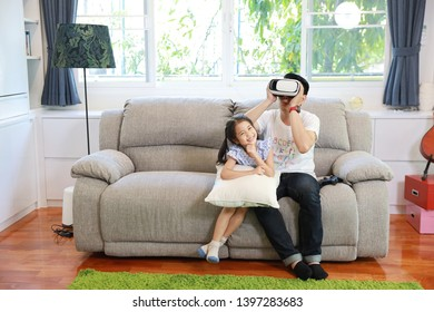 Happy Asian family, father and daughter playing virtual reality goggles on the sofa in the living room with happy smiling face (relaxation and technology concept)