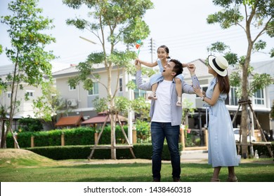 Happy Asian family. Father gave his daughter a piggyback at a park at natural sunlight background and house. Family vacation concept with copy space