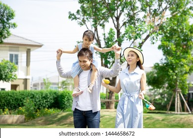 Happy Asian family. Father gave his daughter a piggyback at a park at natural sunlight background and house. Family vacation concept.