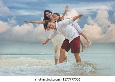 Happy asian family, father, mother, kid, all hands hand up in the airs and play piggyback together with fun along daylight sea beach. Travel, active lifestyle, parents with children on summer vacation