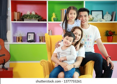 Happy asian family father, mother, child daughter and son sitting on sofa in colorful modern living room with relaxation and smiling face
