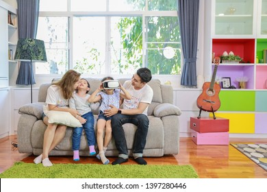 Happy Asian family, father, mother daughter and son playing virtual reality goggles on the sofa in the living room with happy smiling face (relaxation and technology concept)