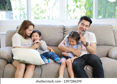 Happy Asian family, father, mother daughter and son singing karaoke on the sofa in the living room with happy smiling face (relaxation and technology concept)