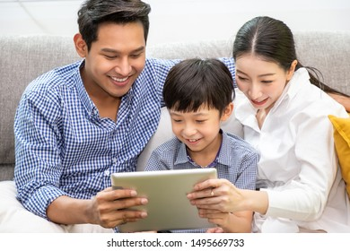 Happy Asian family; father, mother, and son; sitting on sofa using playing tablet together in living room