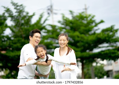 Happy Asian family father and mother holding little asian girl on back smiling playing and having fun moments good time.