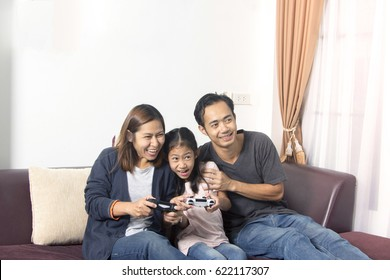 Happy asian family- father, mother and daughter playing a video game at home.
