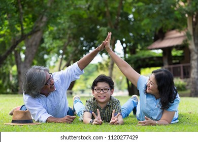 Happy Asian family gesture hand roof over grandchild or kid as house construction goal or protect ,safeguard or Senior Retirement Family Happiness Concept