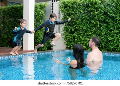 Happy Asian family have fun on swimming pool at summer vacation running and jumping in the pool.