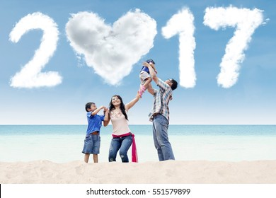 Happy Asian family having fun together at the beach with cloud shaped numbers 2017