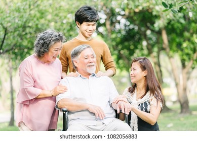 Happy Asian family having a good time together outdoor at the park