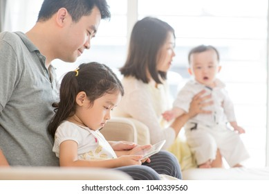 Happy Asian family at home, father and daughter playing tablet pc, natural living lifestyle indoors.
