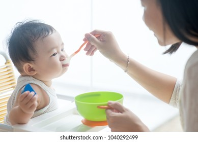 Happy Asian family at home. Mother feeding solid food to 9 months old baby boy in the kitchen, living lifestyle indoors.