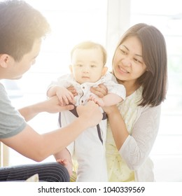Happy Asian family at home, parents and baby, natural living lifestyle indoors.