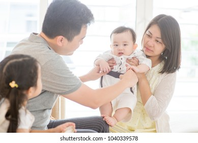 Happy Asian family at home, parents and children, natural living lifestyle indoors.