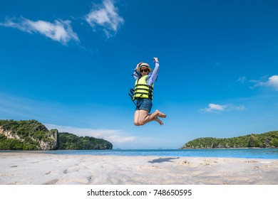 happy asian family jumping together on the beach