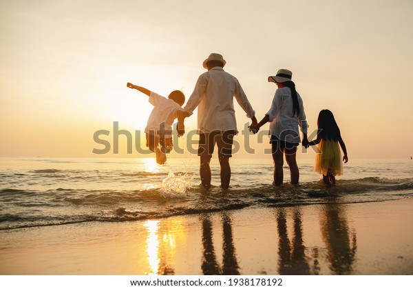 Happy asian family jumping together on the beach in holiday. Silhouette of the family holding hands enjoying the sunset on the  beach.Happy family travel and vacations concept.