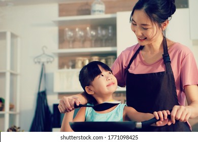 Happy Asian family in the kitchen. Mother and child daughter preparing a meal fried egg.