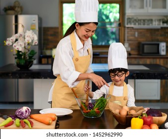 Happy asian family in the kitchen.Mother and son help to make vegetable salad.Mom teaching kid boy cooking healthy salad for dinner.