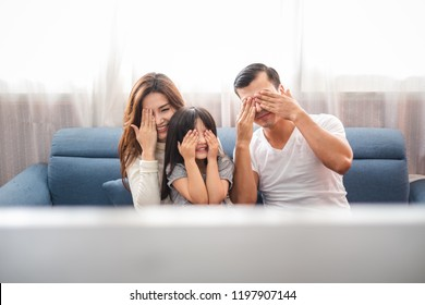 Happy Asian family lifestyle enjoy watching TV scary movies at home