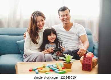 Happy Asian family lifestyle enjoy playing game and watching TV at home