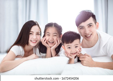 Happy asian family lying on  bed together in the bedroom