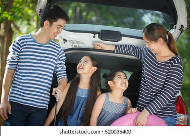 Happy Asian family with mini van are smiling and preparing for travel on vacation