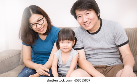 Happy Asian family, Mom Dad and daughter sitting in the living room