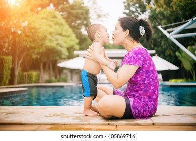 Happy asian family of mother and baby playing in the pool