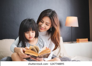 Happy Asian family mother and daughter on bed in bedroom say good night before sleep