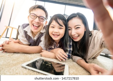 happy Asian Family mother father and daughter making a selfie photo while use digital tablet in living room home background.