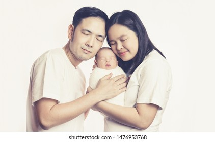 Happy Asian family of mother father and baby son in the studio shooting portrait embrace together smiling with eyes closed. Parenthood and family relationship concept.