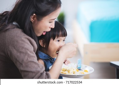 Happy asian family, Mother Feeding Her Baby Girl with a Spoon. Mother Giving Food to her adorable Child at Home. Baby food