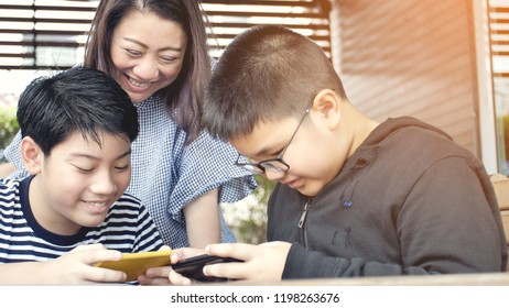 Happy asian family mother and son watching on mobile phone with smile face together.