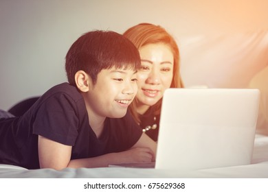 Happy asian family. Mother Son Care communication Laptop Concept  with sun light in the morning at home, Vintage style .
