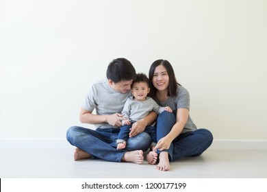 Happy asian family with one baby boy having fun together on floor