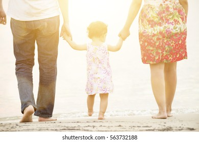 Happy Asian family outdoor activity, holding hands together walking on sandy beach in sunset during vacations.